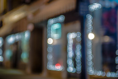 defocused storefront sidewalk lights at night (DigiDreamGrafix.com) Tags: life street city people urban plants motion blur color men fashion horizontal retail architecture youth shopping bag walking asian outdoors person town store blurry bush women asia image contemporary board crowd group culture blurred scene busy commercial promenade storefront signage merchandise activity groceries consumerism buying accessibility defocus striding unrecognizable