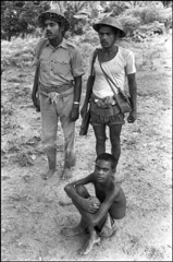 Bengali Refugee Camp in India, 1971 (liberationwarbangladesh.org) Tags: army exterior faces refugee barefoot groupofpeople extérieur groupe calcutta barechest soldat masculin torsenu arméedeterre battledress safetyhelmet piednu réfugié indiaall manallages soldierarmy indetout man25to45years casquedesécurité tenuedecombat asiansouthasianorigin teenageboy13to18yearsold adolescent13to18yearsold homme25à45ans asiatiquedelasiedusud jeunegarçon13à18ans bangladeshwarofindependence adolescentde13à18ans bangladaisnationalité bangladeshinationality guerredindépendancedubangladesh