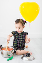 Asian child playing a chef hand holding balloon at home. (Nuiiko) Tags: people food white house playing cute home cooking kitchen girl hat childhood recipe asian fun person japanese baking kid healthy holding child hand little eating interior small joy gray balloon chinese paddle cook adorable lifestyle korean homemade human chef thai meal pan ideas job enjoyment preparation creep preparing concepts ingredient occupation
