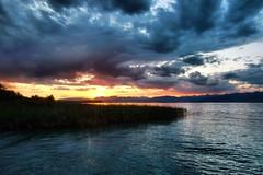 Lake Garda (Erich Hochstöger) Tags: italien sunset italy sun lake mountains reed water clouds landscape see evening abend wasser waves sonnenuntergang horizon wolken berge landschaft sonne horizont schilf lakegarda abendsonne wellen abendrot gardasee abendstimmung eveningmood