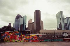 93060021 (alexdotbarber) Tags: slr film skyline analog 35mm mural wiley f8 kodakgold100 1125 downtownhouston colornegative therefinery olympusom2s houstonstreetart olympusomzuiko28mmf35