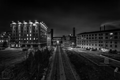 Brick and Iron (CJ Schmit) Tags: longexposure nightphotography railroad sky urban blackandwhite bw monochrome wisconsin clouds canon buildings lights lowlight industrial traintracks smokestacks milwaukee renovation mke shutterdrag creambricks canonef1740mmf40lusm canon5dmarkiii cjschmit 5dmarkiii wwwcjschmitcom niksilverefex2 cjschmitphotography