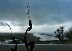 Inside Looking Out (john atte kiln) Tags: uk sea england beach window wet rain palms surf waves unitedkingdom britain ominous curves horns deer devon rainy raindrops surfers inside impressions abstracts figures sculptures darkclouds badweather sauntonsands widebeach foulweather