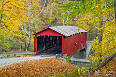 Autumn at Rolling Stone Covered Bridge (Kenneth Keifer) Tags: road county wood old bridge autumn trees red color fall nature beautiful leaves rural creek forest vintage landscape countryside wooden october midwest colorful crossing rustic scenic indiana historic foliage sycamore covered infrastructure coveredbridge americana span oldfashioned roadway yesteryear putnam truss putnamcounty burrarch bigwalnutcreek rollingstonecoveredbridge