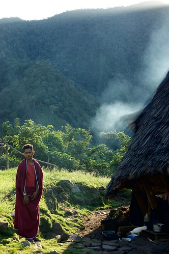 Man standing in from of traditional house - Wae Rebo village (Flores, Indonesia)