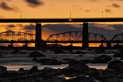 st. marys rapids sunset (twurdemann) Tags: longexposure bridge sunset water spring rocks saultstemarie internationalbridge stmarysriver neutraldensityfilter unitedstatesborder nikcolorefex canadaborder tonalcontrast stmarysrapids camelbacktruss hoyandx8 internationalrailroadbridge 06ndhardgrad reflectorefex gnd2h fujixe1 leeseven5 xf55200mm