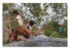one giant leap (handheld-films) Tags: travel india playing water girl children fun jump technology drink indian photojournalism documentary games villages pump refreshing leap leaping waterpipe countrylife pumping subcontinent madhyapradesh communal ruralindia