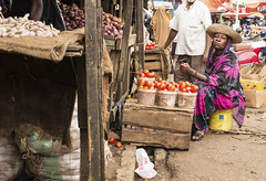 Pemba, Zanzibar, Tanzania - 7 October 2015: African woman wearing traditional clothes selling tomatoes in a local market. (The Nile Basin Initiative Secretariat) Tags: poverty life africa street people food woman fish black vegetables hat shop fruit female rural shopping tanzania person women colorful village market sale african south traditional tomatoes poor culture fresh clothes business exotic trading vendor local zanzibar ethnic trade selling seller stalls ethnicity pemba tanzanian