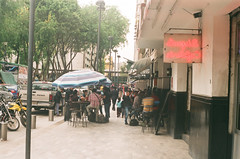 Afeternoon (TheKinkyKid) Tags: street people urban analog umbrella table mexico iso200 cafe lomo alley mexicocity fuji lofi vivitar streetphography filmisnotdead vivitarv3000 fujifilmproplusii200 filmfilmforever analogphography urbanphotgrahy