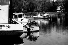 Tied Up (Cheryl Atkins) Tags: blackandwhite water reflections boats mono