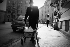 Glowing man - strong rim light - Fujifilm x100t Monochrome + Red filter - street and travel (polybazze) Tags: old shadow sun man face glow fuji stroller pavement fujifilm rim malm hipshot redfilter rimlight x100t