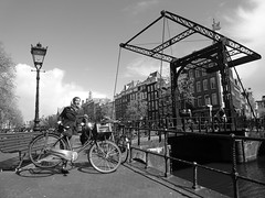 Parking in Amsterdam. (Flyingpast) Tags: street old bridge vacation people blackandwhite bw holiday holland water netherlands monochrome amsterdam bicycle architecture canal pretty cyclist outdoor transport ironbridge lamppost citybreak wb2000 tl350