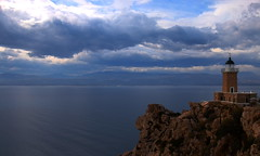 Standing alone... (Michael Kalognomos) Tags: blue sea lighthouse storm water canon landscape eos rocks tall 24105 loutraki 70d