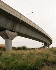 west-melbourne-0206-ps-w (pw-pix) Tags: bridge trees red plants white signs grass concrete lights weeds funny columns australia melbourne victoria safety tape freeway hanging ribbon poles tollway amusing pylons dangling shrubs containers supports boltebridge citylink westmelbourne innersuburbs offfootscrayroad boltebridgeonramp boltebridgeofframp underboltebridgeonramps underboltebridgeofframps