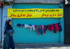 woman passing in front of a wall of kindness created to give clothes for free to poor people, Central County, Yazd, Iran (Eric Lafforgue) Tags: poverty street charity people woman horizontal outdoors photography women asia iran muslim homeless poor persia social womenonly clothes help solidarity dailylife adultsonly oneperson middleeastern yazd youngadultwoman onewomanonly   1people  iro  centralcounty colourpicture  irandsc08137