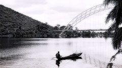 on the Volta, Ghana (Pejasar) Tags: africa bridge people blackandwhite man contrast boat canoe ghana westafrica delivery firewood volta