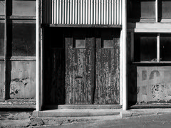 Look at that (duncanmc42) Tags: door old windows newzealand blackandwhite bw mouth graffiti blackwhite eyes peeling doors olympus doorway southisland bandw blacknwhite flaky bnw heritagebuilding oamaru em5 microfourthirds duncancunningham ilobsterit duncamc42