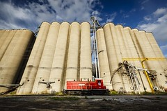 Glasgow Grain Elevators (Notley) Tags: railroad sky usa clouds rural river spring midwest afternoon glasgow tracks engine rail wideangle silo missouri april silos trainengine warmlight railroadtracks afternoonlight howardcounty 2016 10thavenue glasgowmissouri ruralphotography howardcountymissouri missouriphotography httpwwwnotleyhawkinscom notleyhawkinsphotography redtrainengine