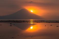 Hiding Behind (Guillaume Desfeux) Tags: sunset sea sky bali orange sun mountains reflection clouds indonesia volcano rocks outdoor autofocus