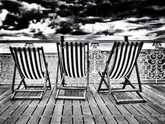 Waiting for summer (pj_warlock) Tags: sky bw white storm black brighton deckchair