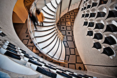 Descending the Spiral Tate Britain (Edwinjones) Tags: city uk greatbritain light england people urban motion blur reflection building london glass lines stone museum architecture modern stairs photoshop reflections hall movement europe unitedkingdom interior curves wideangle down line indoors staircase gb banister lookingdown elegant curve vignetting vignette spiralstaircase tatebritain chequered urbanmuseum tonemapping dslra700