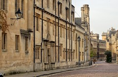 Early morning, quiet residential street, Oxford, England (edk7) Tags: city uk roof england urban sculpture building tower architecture cityscape arch stonecarving nikond50 cobblestone sidewalk oxford oxfordshire 2007 roadway universityofoxford oldstructure crenelations orielwindow edk7 italianateroundarch