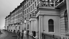 Adelaide Crescent, Hove. (ManOfYorkshire) Tags: bw monochrome stone seaside construction streetlight uniform terrace hove 1800s crescent adelaide seafront curve railings doubleyellowlines bollards brightonhove castellation