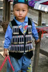 Boy wearing ethnical decorated vest, Hmong village near Luang Prabang, Laos (inchiki tour) Tags: travel boy portrait people photo asia southeastasia village embroidery traditional cloth laos ethnic luangprabang hmong stitchwork  louangphrabang