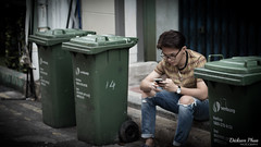 A man and his three green bins (gunman47) Tags: street people man green field night trash relax asian photography 50mm eyes singapore asia thought bokeh f14 candid smoke albert deep running tourist smoking bin east changer stop photograph rush lane bubble shallow moment friday sg haji depth bins decisive streetside sembcorp