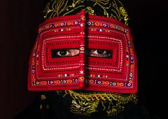 a bandari woman wearing a traditional mask called the burqa, Hormozgan, Minab, Iran (Eric Lafforgue) Tags: red portrait people woman beauty horizontal closeup golden persian clothing eyes asia veil mask iran muslim islam religion hijab culture persia headshot hidden indoors covered iranian adultsonly oneperson traditionaldress burqa customs middleeastern frontview sunni burka chador 20sadult youngadultwoman balouch darkbackground hormozgan onewomanonly lookingatcamera burqua  bandari  1people  iro thursdaymarket  minab colourpicture  borqe panjshambebazar boregheh irandsc06690