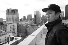 Rooftop contemplation (Eric Flexyourhead (shoulder injury, slow)) Tags: city roof portrait urban bw canada man guy rooftop monochrome skyline vancouver buildings japanese blackwhite friend downtown bc view britishcolumbia dude ricohgr shogo shallowdepthoffield hastingsstreet westhastings 510westhastings