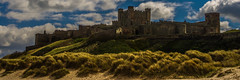 Bamburgh Castle Above Sand Dunes (Brian Travelling) Tags: old blue england cloud green castle heritage grass weather stone architecture clouds landscape outdoors sand bright pentax outdoor dunes bluesky historic northumberland bamburgh pentaxkr