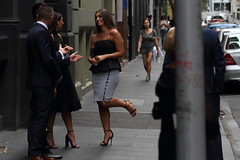 Standing on one foot (drez5mond) Tags: street city people urban woman smile dress candid group skirt well heels talking dressed