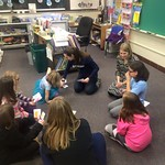 Students helping elementary students in a classroom