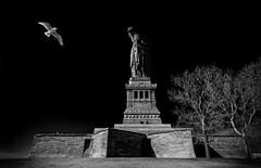 The Statue of Liberty (Darren LoPrinzi) Tags: city nyc newyorkcity urban blackandwhite bw ny newyork bird sol monochrome statue canon dark liberty island mono fly flying blackwhite newjersey nj landmark icon 5d hudsonriver canon5d hudson statueofliberty lowkey iconic lowermanhattan miii libertyisland ladyliberty