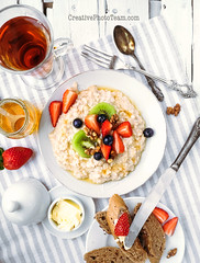 Oat porridge with fresh berries and honey (CreativePhotoTeam.com) Tags: morning food white home cup glass closeup fruit breakfast vintage bread table dessert countryside daylight wooden milk healthy natural tea sweet toast rustic grain cereal knife tasty fork spoon bowl fresh gourmet oatmeal delicious health honey butter snack meal vegetarian sweets organic diet tablecloth cooked porridge oat nutrition muesli brekfast