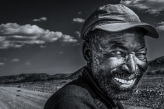 Wicked! (Axel Halbgebauer) Tags: africa street travel portrait blackandwhite bw man hot smile face hat closeup zeiss dark eyes close desert emotion expression sony teeth ngc wideangle headshot cap grinning fe namibia a7