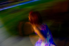 let's move (KevinIrvineChi) Tags: park blue red orange chicago playing blur green floral girl grass night fence dark hair print lights blurry long shadows play dress arms action outdoor sony blurred running chicagoist dscrx100