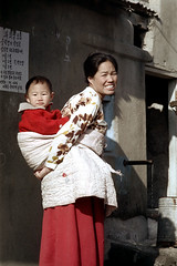 31-350 (ndpa / s. lundeen, archivist) Tags: city winter boy people woman snow color fall film smile smiling 35mm child rooftops candid nick mother citylife streetphotography streetlife pedestrian korea roofs korean seoul blanket 1970s southkorea 1972 31 youngwoman motherandchild carry carrying lightsnow womanandchild dewolf onfoot onherback nickdewolf photographbynickdewolf reel31