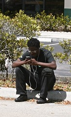 Black man waiting with headphones (LarryJay99 ) Tags: glasses hands arms candid fingers westpalmbeach dude canoe blackpeople blackman headphone earbuds iphone unsuspecting canonefs60mmf28macrousm xti seatedman handsaround floridamanatees ilobsterit canonefs60mmf28macrousa