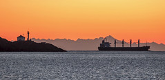 Outbound (Paul Rioux) Tags: morning lighthouse mountains sunrise ship bc britishcolumbia scenic vessel victoria daybreak freighter bulkcarrier juandefucastrait salishsea trialisland