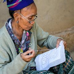 A woman stitching a cloth, Hmong village near Luang Prabang, Laos (inchiki tour) Tags: travel portrait people art photo asia southeastasia village handmade embroidery traditional souvenir cloth laos ethnic luangprabang hmong handcraft  stitchwork   fablic louangphrabang