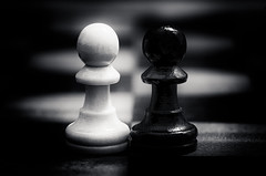 We are either kings or pawns... (zzra) Tags: bw white black macro contrast dark pieces opposite chess pinhole pawn