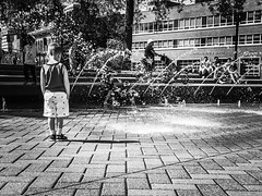 Keeping Your Shadow Dry (TMimages PDX) Tags: park street city people urban blackandwhite fountain monochrome buildings portland geotagged photography photo child image streetphotography streetscene sidewalk photograph pedestrians pacificnorthwest vignette fineartphotography iphoneography