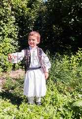 Romanian Peasant Child (kalypsoworldphotography) Tags: park travel boy portrait art nature smile grass fashion festival proud youth rural vintage garden countryside costume belt village child outdoor handmade folk background traditional country culture posing folklore patriotic icon textile national romania historical curious tradition transylvania ethnic regional romanian peasant caucasian ethnology ardeal poienitavoinii