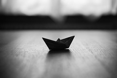 """""""Paper Boat"""" (helmet13) Tags: d800e raw bw paperboat selectivefocus bokeh woodentable window curtain backlight conceptual world100f heartaward peaceaward platinumpeaceaward 200faves gettyimages simplicity"""