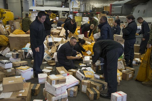 Sailors sort through mail received during replenishment at sea in the hangar bay of USS Bonhomme Richard.