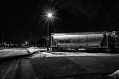 Yielded Crossing (CJ Schmit) Tags: road longexposure nightphotography railroad winter blackandwhite bw snow cold monochrome wisconsin train canon lowlight streetlight industrial milwaukee traincars mke shutterdrag starlights jonesisland canonef1740mmf40lusm canon5dmarkiii cjschmit 5dmarkiii wwwcjschmitcom niksilverefex2 cjschmitphotography