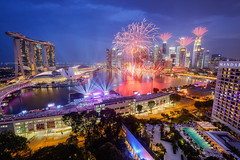 Joyful Display (Scintt) Tags: show city travel bridge blue light sky urban tourism skyline architecture modern night clouds marina buildings point photography hotel evening bay hall office high jon singapore long exposure carlton day mood glow cityscape slow place fireworks crowd platform dramatic surreal floating parade arena celebration national hour shutter ndp ritz mandarin cbd helix tall rays oriental sands expensive chiang exploration iconic exclusive futuristic vantage joyous mbs raffles pagar tanjong 2015 scintillation sg50 scintt ndp15