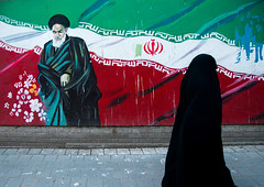 veiled woman passing in front of propaganda sign with ayatollah khomeini on the wall of the former u.s. embassy, Central district, Tehran, Iran (Eric Lafforgue) Tags: street portrait people woman usa history horizontal painting beard outdoors artwork mural asia paint unitedstates iran propaganda painted flag muslim islam political politics persia streetscene embassy hero conflict leader iranian tehran revolutionary adultsonly oneperson islamic teheran antiamerica middleeastern imam centraldistrict ayatollah ambassy commemorate khomeini onewomanonly   1people  denofespionage iro  unrecognizableperson colourpicture  irandsc01310